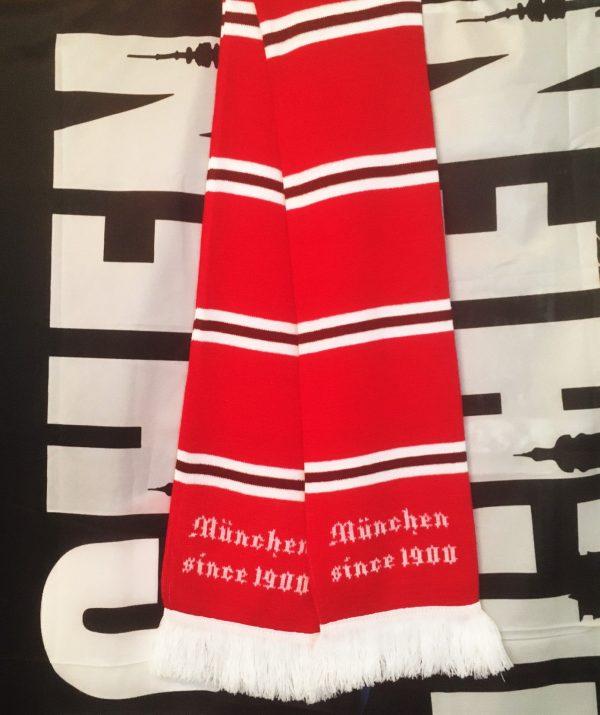 """Balkenschal rot weiß bordeauxrot Der neue Balkenschal ist in einem kräftigen rot mit weißen Balken, die wiederrum mit bordeauxroten Balken durchzogen sind, in einem ansprechnedem Design gehalten. An den Schalenden ist der Schriftzug """" München since 1900"""" eingestrickt. Mateial 100% Acryl"""