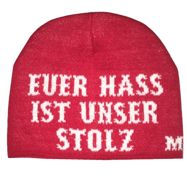 """Mütze """"Euer Hass ist unser Stolz"""" in rot Mütze """"Euer Hass ist unser Stolz"""" in Rote Strickmütze mit weißer Aufschrift """"München Euer Hass ist unser Stolz"""". Einheitsgröße Material: 100% Acryl Die Mütze """"München Euer Hass ist unser Stolz"""" war bisher nur an unserem Fanshop im U-Bahnhof Fröttmaning bei Heimspielen des FC Bayern München erhältlich. Ab jetzt gibt es diesen München Fanartikel für Euch auch in unserem Online-Shop. Wenn Ihr diese Mütze bestellen solltet, haltet sie (sowie auch Euere anderen roten Fansachen) immer in Ehren! Dieser Fanartikel ist mit viel Leidenschaft und Herzblut von unserem Fan-Point Team entworfen worden und hält von seiner Qualität her ewig. Einige von uns sind schon seit 1972 oder länger dabei, andere noch nicht so lange, oder manche erst relativ neu, aber alle sind rot bis unters Dach. Die ersten eigenen Fanartikel stellten wir damals im Olympiastadion her und 1994 haben wir dann unseren ersten Verkaufsstand am Oly gehabt. Für uns gilt es also wirklich """"rot und weiss – ein Leben lang"""". Wir versuchen ständig zusammen mit unseren Produzenten die Qualität und die Designs zu verbessern. Das herstellen von rot-weissen Fanartikeln für uns nicht einfach ein Beruf, """"nein"""" es ist eine Berufung und unsere größte Freude ist, wenn sie Euch gefallen. Euer Fan Point Team."""