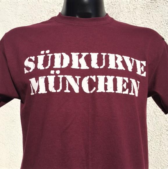 """T-Shirt Südkurve München in bordeauxrot Auf das neue T-Shirt Südkurve in bordeauxrot bekommt Ihr gleich mal 20% Rabatt. Material: 100 % Cotton/Baumwolle Dieses Südkurve München T Shirt war bisher nur an unserem Fanshop im U-Bahnhof Fröttmaning bei Heimspielen des FC Bayern München erhältlich. Ab jetzt gibt es diesen München Fanartikel für Euch auch in unserem Online-Shop. Wenn Ihr dieses T-Shirt bestellen solltet, haltet es (sowie auch Euere anderen roten Fansachen) immer in Ehren! Dieser Fanartikel ist mit viel Leidenschaft und Herzblut von unserem Fan-Point Team entworfen worden und hält von seiner Qualität her ewig. Einige von uns sind schon seit 1972 oder länger dabei, andere noch nicht so lange, oder manche erst relativ neu, aber alle sind rot bis unters Dach. Die ersten eigenen Fanartikel stellten wir damals im Olympiastadion her und 1994 haben wir dann unseren ersten Verkaufsstand am Oly gehabt. Für uns gilt es also wirklich """"rot und weiss – ein Leben lang"""". Wir versuchen ständig zusammen mit unseren Produzenten die Qualität und die Designs zu verbessern. Das herstellen von rot-weissen Fanartikeln für uns nicht einfach ein Beruf, """"nein"""" es ist eine Berufung und unsere größte Freude ist, wenn sie Euch gefallen. Euer Fan Point Team."""