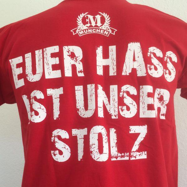 """T-Shirt """"Euer Hass ist unser Stolz""""Rotes Kult T-Shirt """"München - Euer Hass ist unser Stolz"""" mit zwei Motivseiten.Der Klassiker unter den München Fan-Shirts.Material: 100% Cotton/BaumwolleDas T-Shirt """"Euer Hass ist unser Stolz"""" war bisher nur an unserem Fanshop im U-Bahnhof Fröttmaning bei Heimspielen des FC Bayern München erhältlich. Ab jetzt gibt es diesen München Fanartikel für Euch auch in unserem Online-Shop. Wenn Ihr dieses T-Shirt bestellen solltet, haltet es (sowie auch Euere anderen roten Fansachen) immer in Ehren! Dieser Fanartikel ist mit viel Leidenschaft und Herzblut von unserem Fan-Point Team entworfen worden und hält von seiner Qualität her ewig. Einige von uns sind schon seit 1972 oder länger dabei, andere noch nicht so lange, oder manche erst relativ neu, aber alle sind rot bis unters Dach. Die ersten eigenen Fanartikel stellten wir damals im Olympiastadion her und 1994 haben wir dann unseren ersten Verkaufsstand am Oly gehabt. Für uns gilt es also wirklich """"rot und weiss – ein Leben lang"""". Wir versuchen ständig zusammen mit unseren Produzenten die Qualität und die Designs zu verbessern. Das herstellen von rot-weissen Fanartikeln für uns nicht einfach ein Beruf, """"nein"""" es ist eine Berufung und unsere größte Freude ist, wenn sie Euch gefallen.Euer Fan Point Team.* München T-Shirt """"Euer Hass ist unser Stolz"""""""